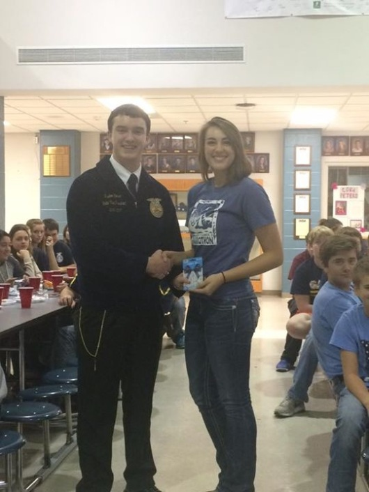 Katie McCauley won the section dessert contest with her peach pie entry. Illinois FFA Vice-President Paxton Morse presented Katie with a $ 25 gift card.